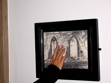 Mãos tateando foto em relevo.