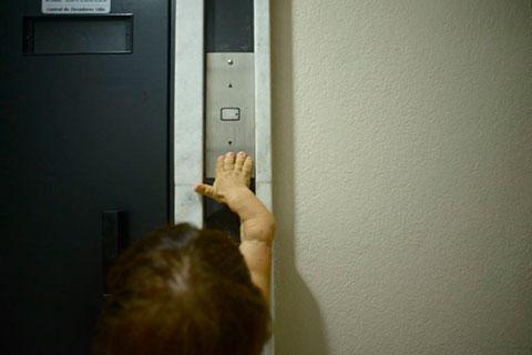 Tentando alcançar o botão do elevador.