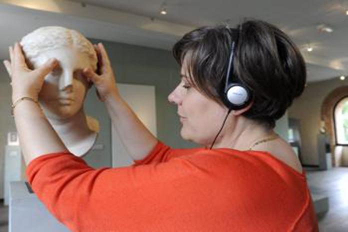 Mulher com fones de ouvidos tateando escultura.