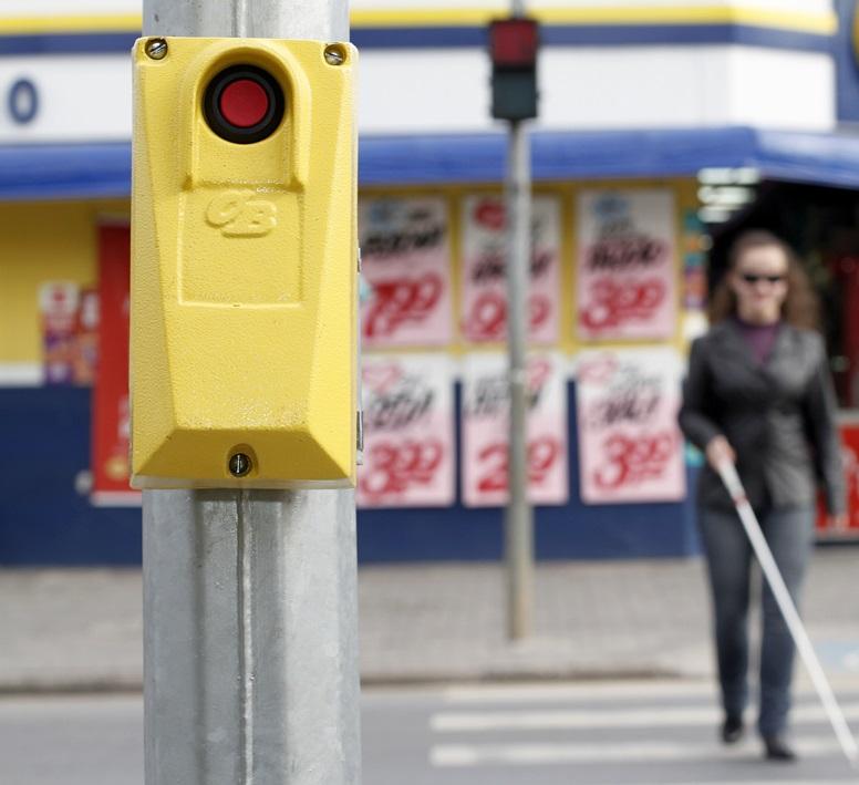 Mulher cega atravessando a rua. Em foco, uma botoeira.